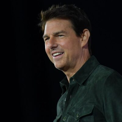 Tom Cruise smiling in a green shirt