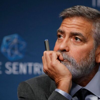 George Clooney in a suit holding a pen