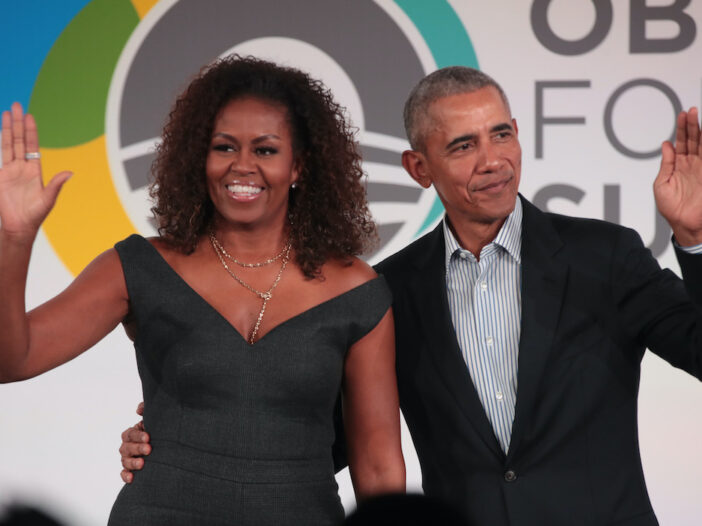 Barack Obama and Michelle Obama waving to a crowd