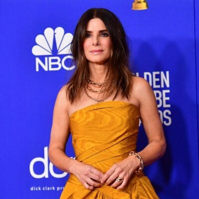 Sandra Bullock in a yellow dress against a blue background