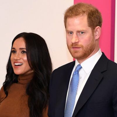Prince Harry in a black suit with Meghan Markle in a tan sweater