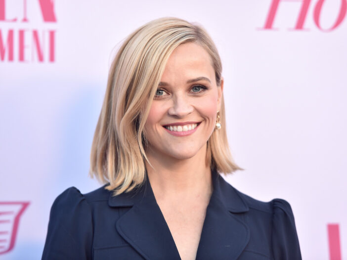 Reese Witherspoon smiling in a blue jacket