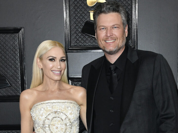Gwen Stefani in a white dress smiling with blake shelton in a black suit