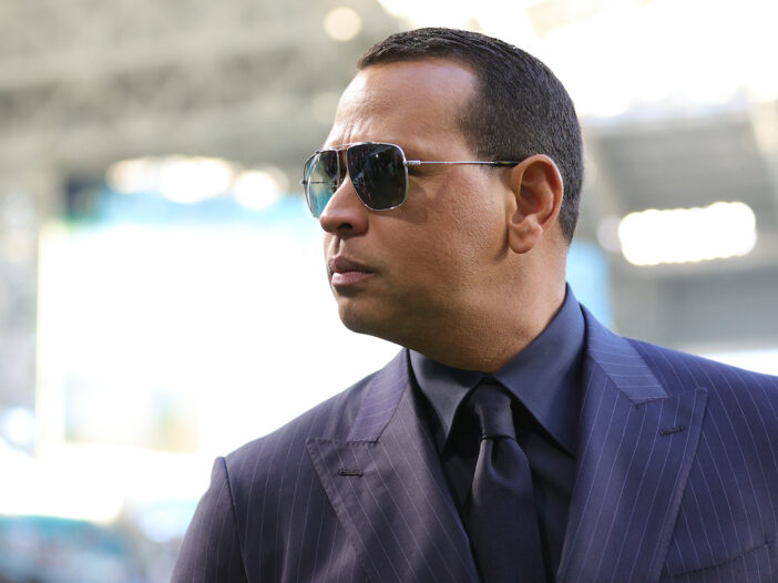 Alex Rodriguez in a grey blue suit and sunglasses