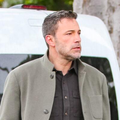 Ben Affleck in a tan coat and grey shirt