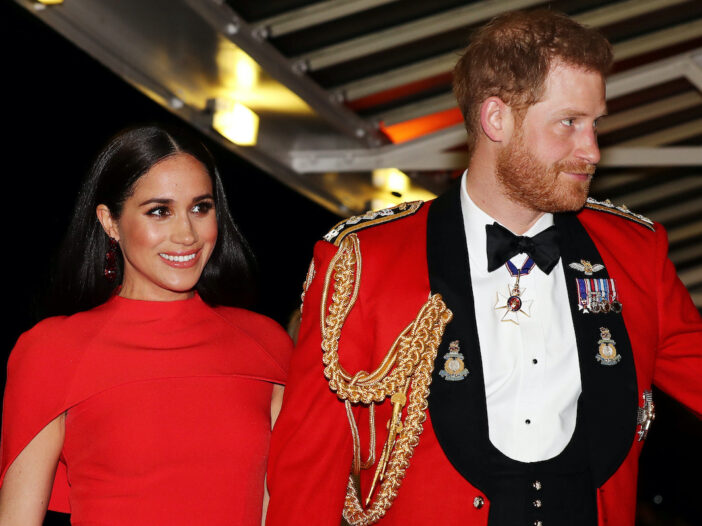 Meghan Markle in a red dress with Prince Harry in a red tux