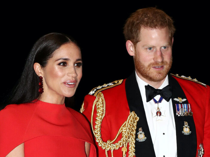 Prince Harry in a red tuxedo and Meghan Markle in a red dress