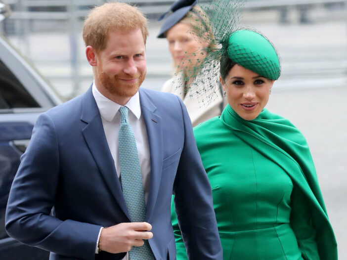 Prince Harry in a blue suit with Meghan Markle in a green dress