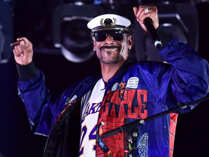 Snoop Dogg DJing on stage in a captain's hat