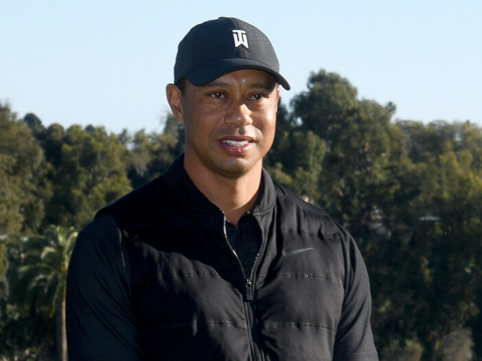 Tiger Woods smiling in a black vest and shirt