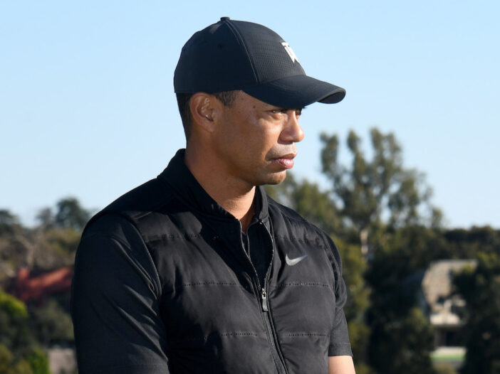 Tiger Woods outdoors in a black hat and shirt