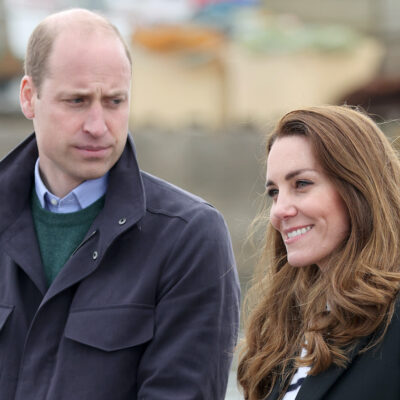 Prince WIlliam in a coat looking at Kate Middleton in a coat
