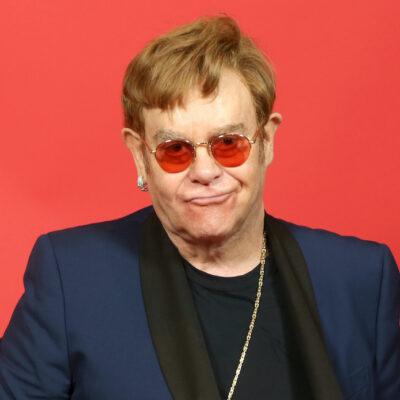 Elton John in a blue jacket