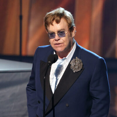 Elton John in a navy suit on stage