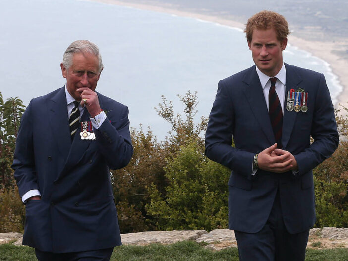 Prince Charles and Prince Harry stand apart from each other in blue suits outdoors