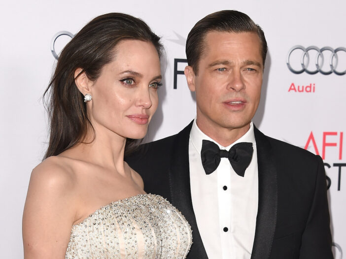 Angelina Jolie in a white dress with Brad Pitt in a tuxedo