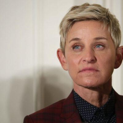 Ellen DeGeneres looking solemn in a red suit