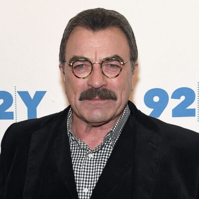 Tom Selleck in a black suit and plaid shirt