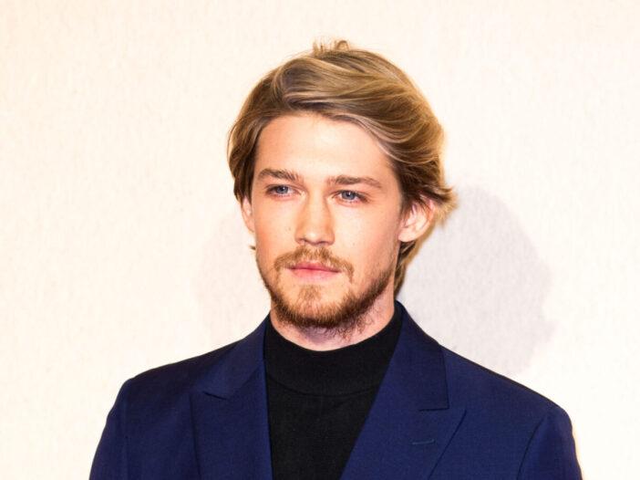 Joe Alwyn with facial hair wearing blue suit jacket