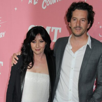 Shannen Doherty and spouse Kurt Iswarienko at a CMT event. She's wearing a black jacket and a white shirt; he has his arm around Doherty and is wearing a grey jacket and white shirt.