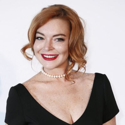 Lindsay Lohan wearing red lipstick and a white pearl necklace