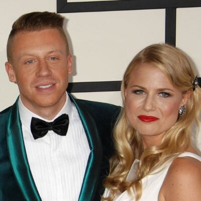 Macklemore and his wife, Tricia Davis at the Grammys in 2015. He's wearing a green suit; she's wearing a white dress.