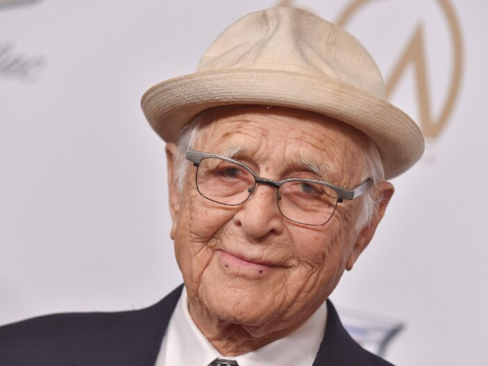 Norman Lear wearing a black suit and a beige hat.