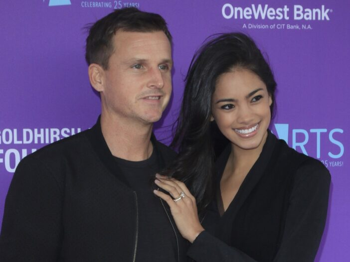 Rob Dyrdek and wife Bryiana Noelle Flores wearing black and standing in front of a purple backdrop.
