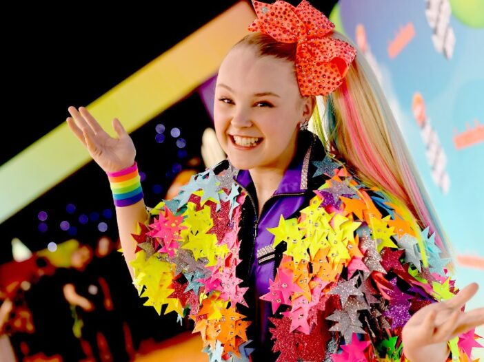 Jojo Siwa wears a colorful star jacket on the red carpet while wearing her usual large hair bow