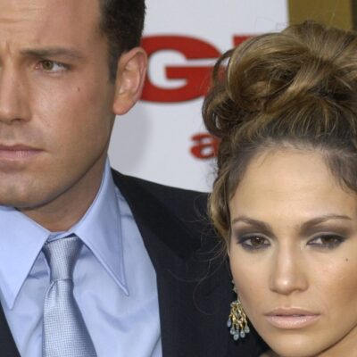 Ben Affleck and Jennifer Lopez look serious with a cutout of Alex Rodriguez looking on in shock in the foreground