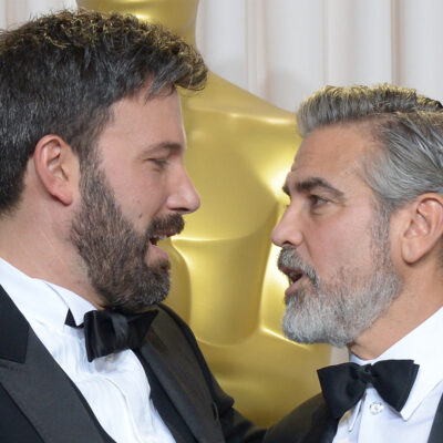 Ben Affleck o the right, looking at George Clooney, who is looking back at Affleck.
