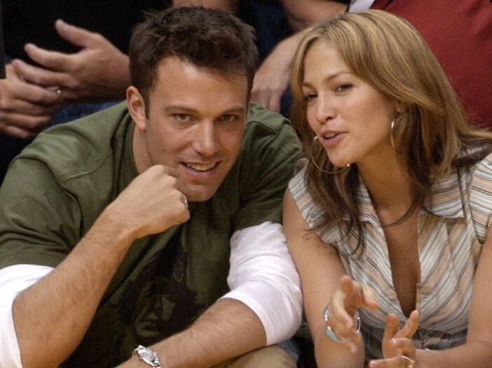 Ben Affleck and Jennifer Lopez lean in close to each other during a basketball game