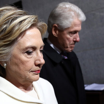Hillary Clinton in the foreground looking dour, Bill Cljnton slightly out of focus in the background.