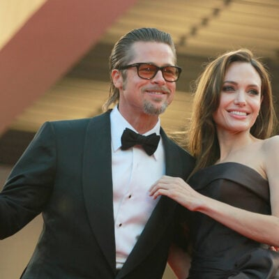 Brad Pitt in sunglasses smiling with Angelina Jolie, back when they were married.
