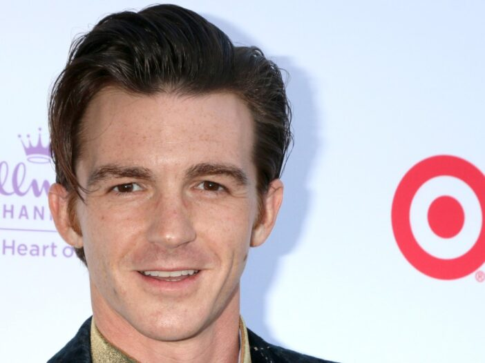 Drake Bell wears a dark suit jacket on the red carpet