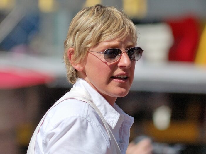 Ellen DeGeneres wears a white shirt and dark sunglasses as she walks out in public