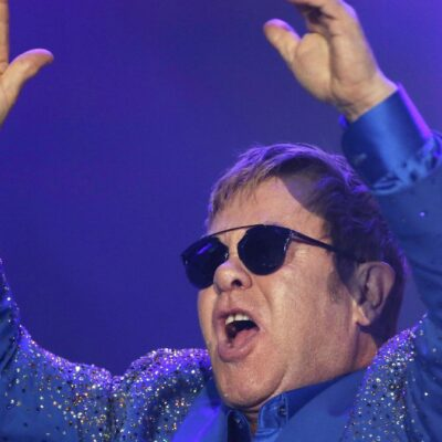 Elton John raises his arms over his head as he performs onstage