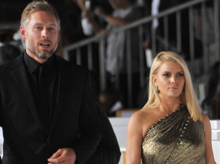 Eric Johnson, wearing a black suit, walks with Jessica Simpson, in a gold gown