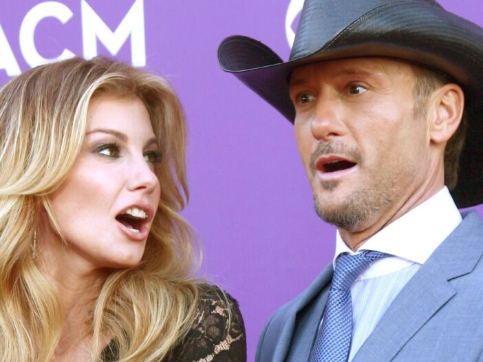 Faith Hill looks at Tim McGraw, who wears a black hat and surprised face