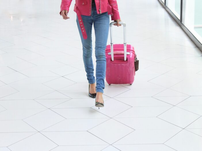 Image of a woman in a pink jacket and jeans rolling a suitcase in an airport.