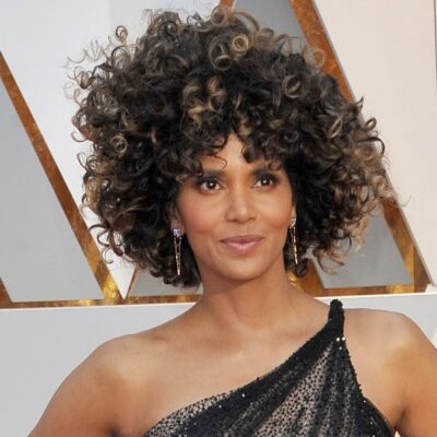 Halle Berry wears a black and gold gown on the red carpet