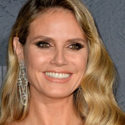 Heidi Klum wears a dress with a plunging neckline against a gray background