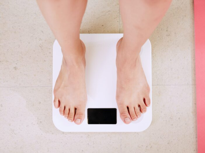 Image of woman weighing herself on a scale.