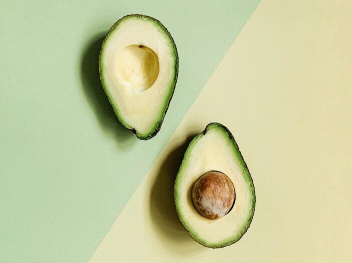 Image of a sliced avocado against a green and yellow background.
