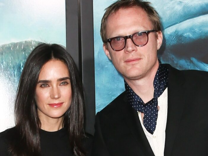 Jennifer Connelly, in a black dress, stands with husband Paul Bettany, in a black suit, on the red carpet