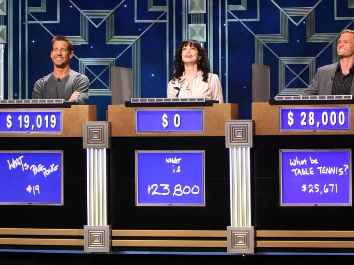 Three celebrity contestants compete on the set of Jeopardy! behind the iconic podiums