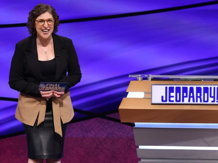 Mayim Bialik laughs on the set of Jeopardy beside an empty podium