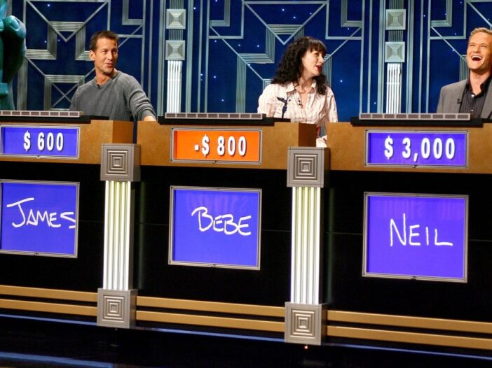 Three celebrity contestants on Jeopardy! laugh together behind their individual podiums