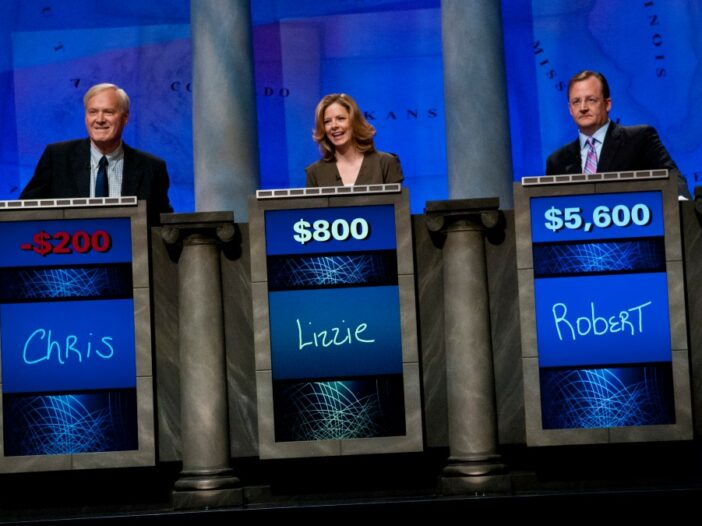Three people stand behind podiums on the set of Jeopardy!