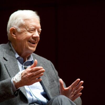 Jimmy Carter sitting in a grey suit and holding his hands out while giving a speech.